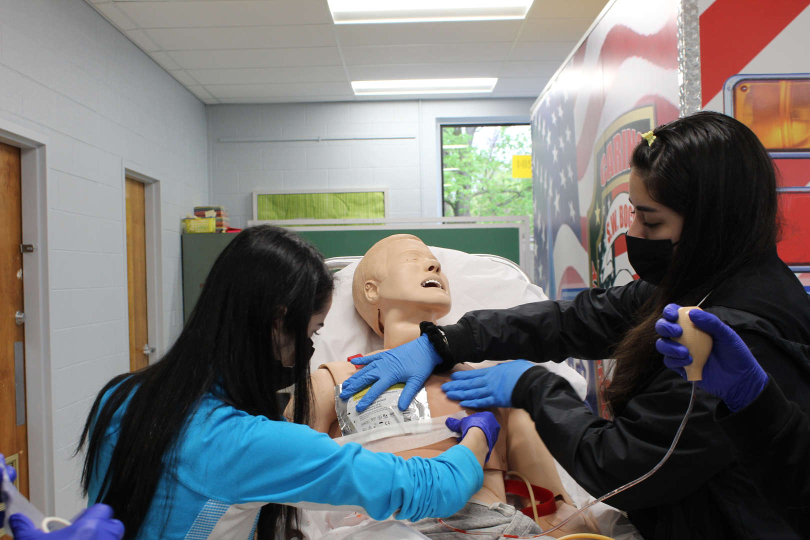 Students practice first aid on a mannequin