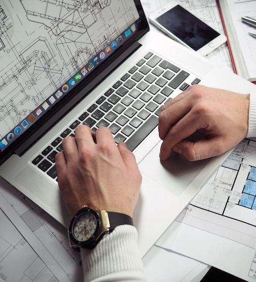 hands at a laptop keyboard and architectural plans on screen