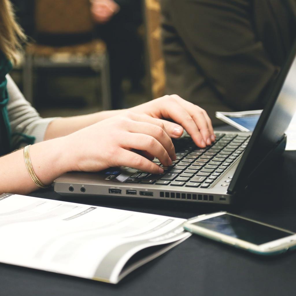 person typing on laptop keyboard