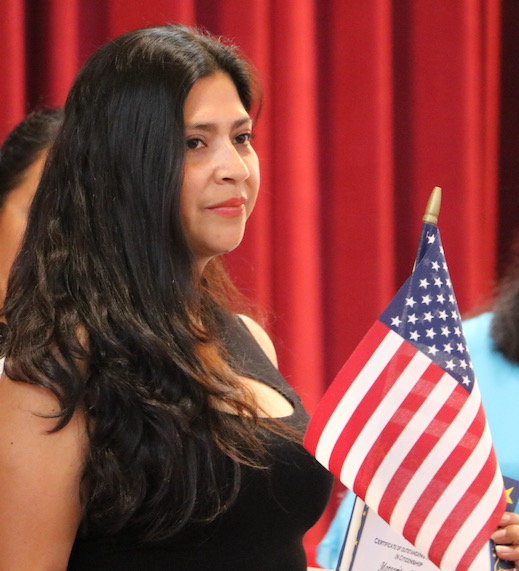 graduate of citizenship program holding a flag
