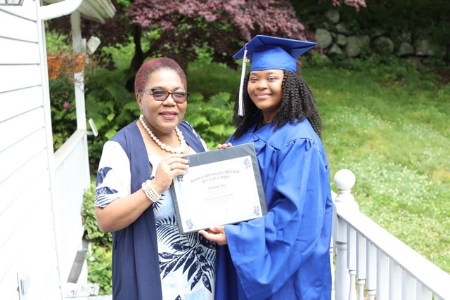 parent and graduate in commencement gown holding diploma
