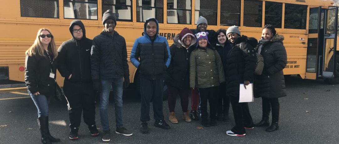 Students and staff in front of the school bus getting ready to board