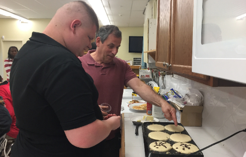 Student and staff adding chocolate chips to the pancakes