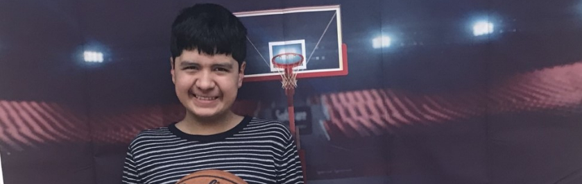 student posing in front of the basketball back drop