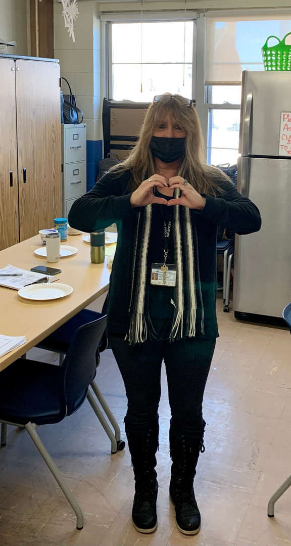 Staff member wearing a sweater  making a heart with their hands
