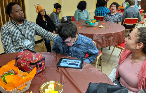 Students with Ipad and staff at table during Thanksgiving Feast