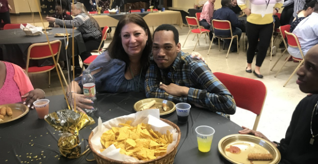 Student and staff at table with a bowl of chips