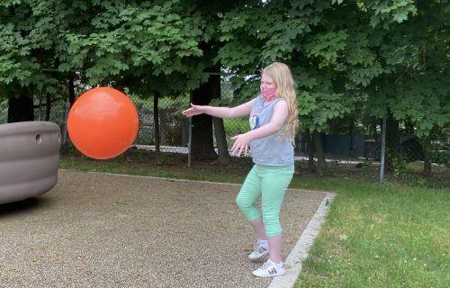 Showcase photo. Girl throwing a big ball.