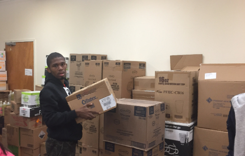 Student in front of a pile of boxes