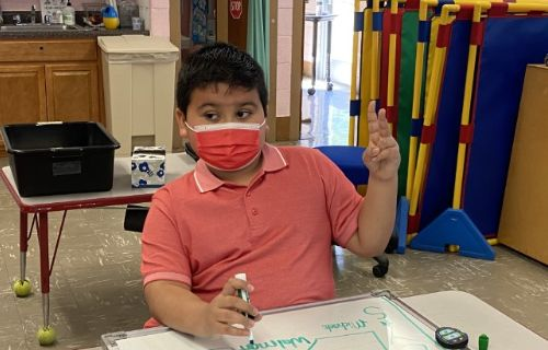 Student at desk wearing a mask signing the number two.
