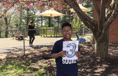 student outside holding 3