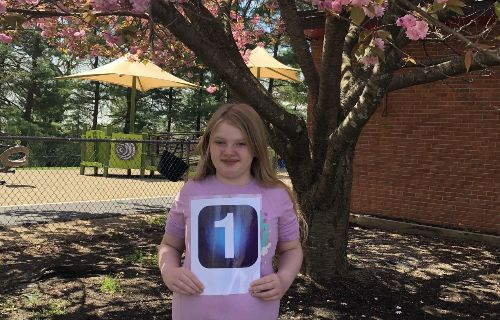 student outside by tree holding 1