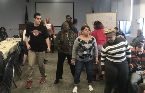 Staff and students dancing in the middle of the room