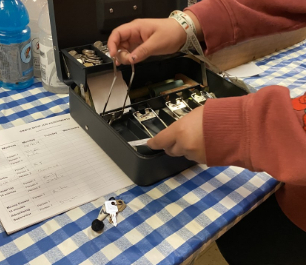 A student handling money with a cash register