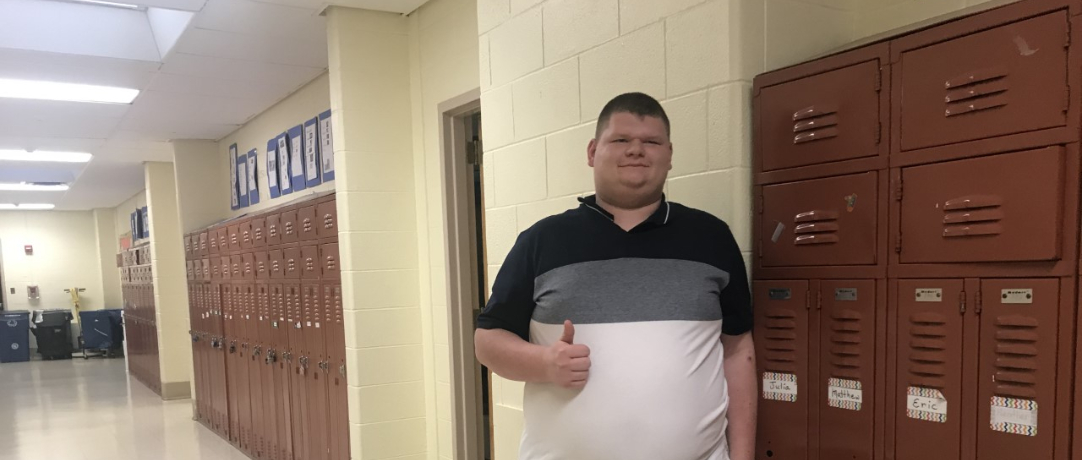 Student giving a thumbs up in the hallway next to his locker