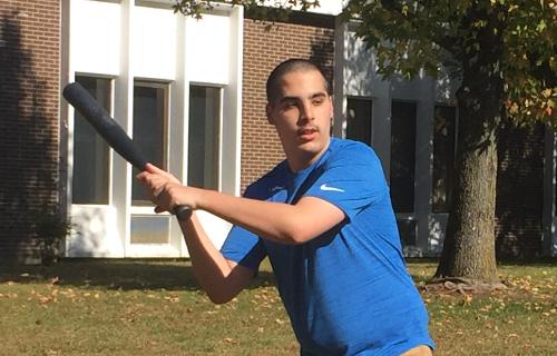 Student playing baseball outside