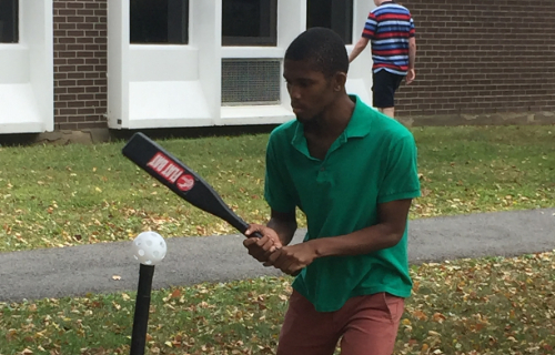 Student playing baseball hitting the ball