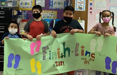 Students in classroom holding their finish line banner.