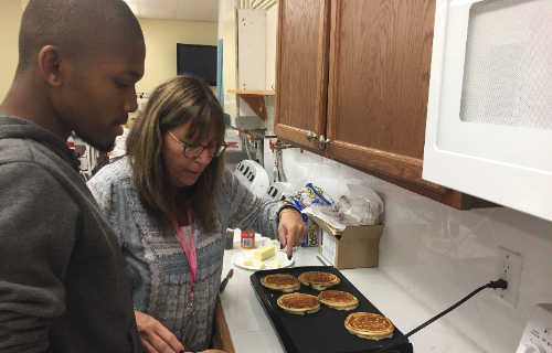 Student and staff cooking pancakes on the griddle