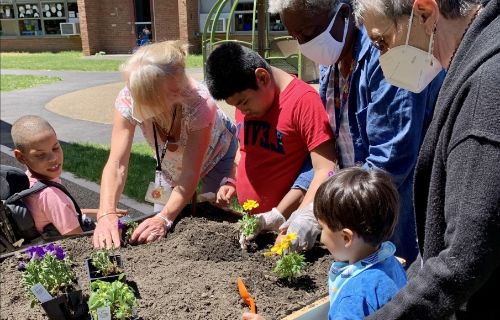 Student and staff working in the garden.