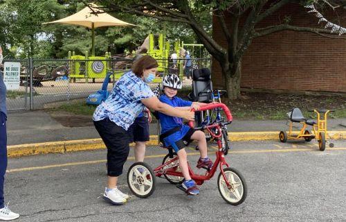 Staff helping student bike ride.