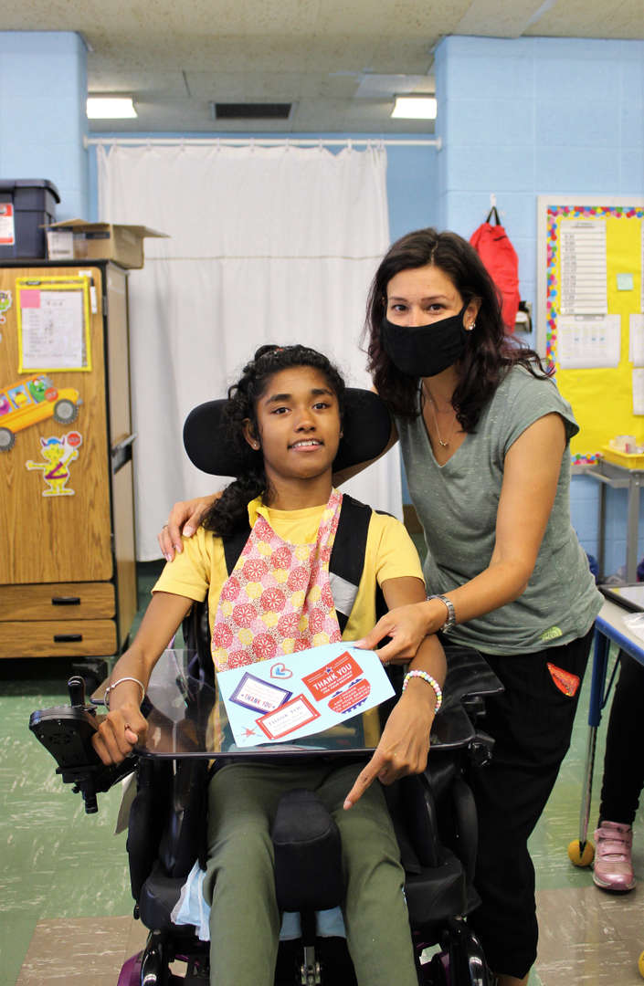 A teacher holds up a female student's card as they pose for a photo.