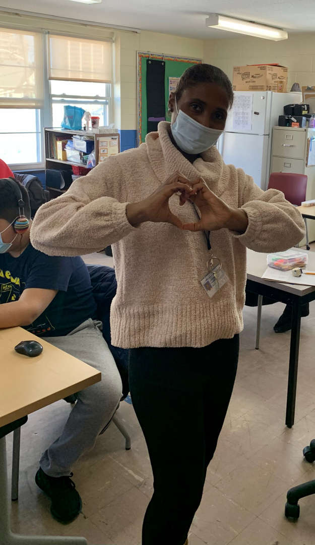 Staff member creates a heart with their hands