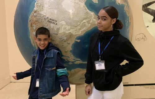 Students in front of globe at the museum