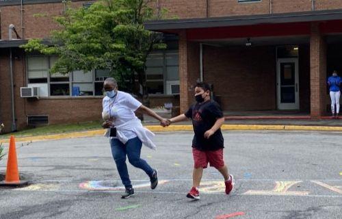 Staff and student running around the circle.