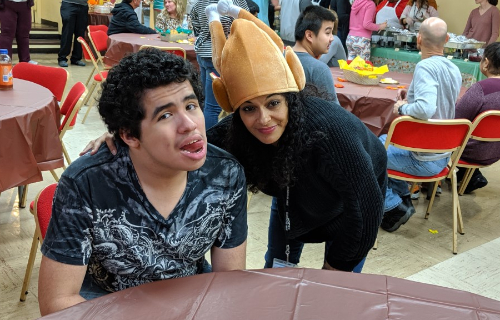 Students and staff wearing a hat at table during Thanksgiving Feast