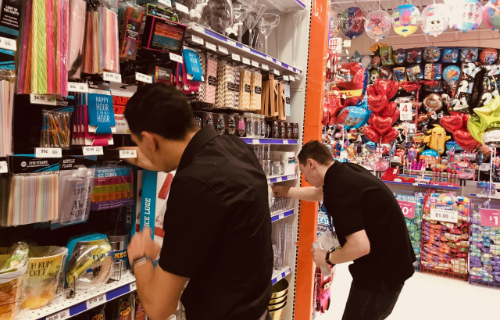 Two students stocking shelves at party city
