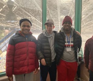 Three students at the recycling recovery facility center smiling