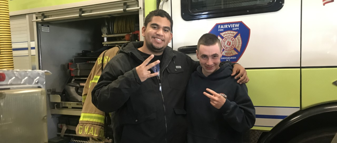 Fire truck and students giving the peace sign