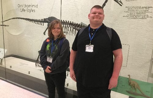 Two students at Museum with Dinosaur Skeleton behind them
