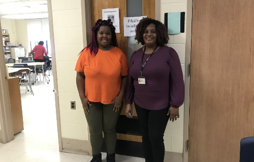 Student and staff smiling while standing in front of the classroom door