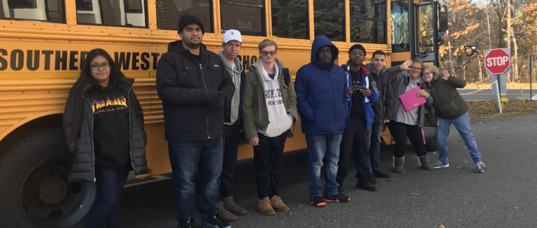 Students and staff in front of the school bus