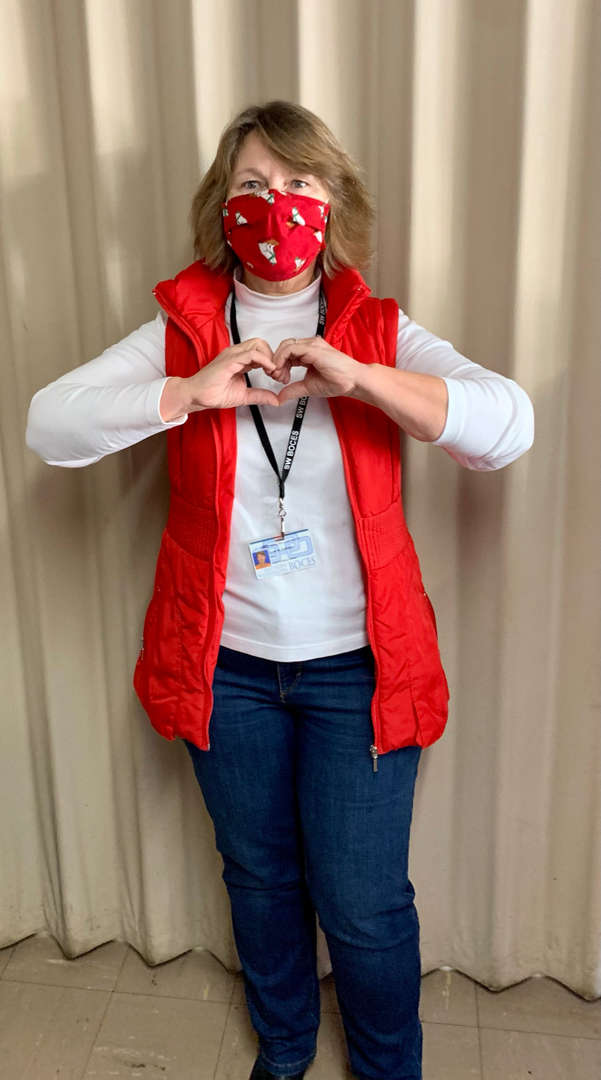 Staff member wearing vest making a heart with their hands