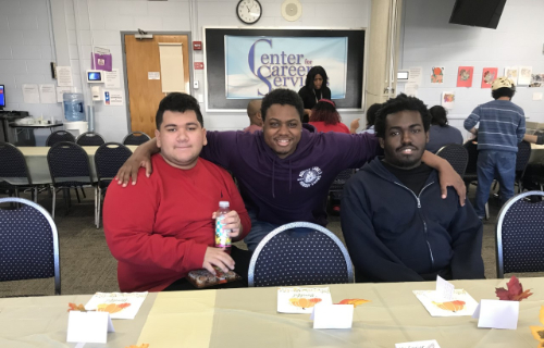 Students sitting in front of the table at Thanksgiving Feast