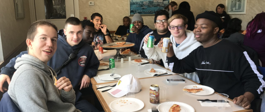 Students and staff eating pizza together at the table
