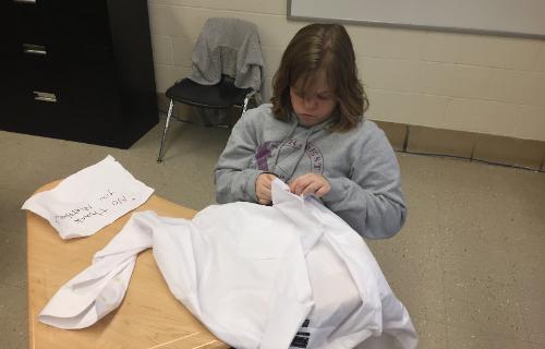 Student sitting at desk folding a white shirt