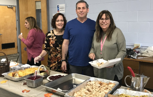 Staff at feast standing in front of the food