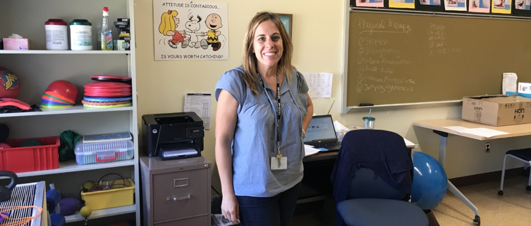 Staff smiling in front of her OT classroom