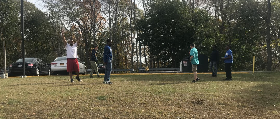 Students playing football in gym class on the grass on the side of the school building