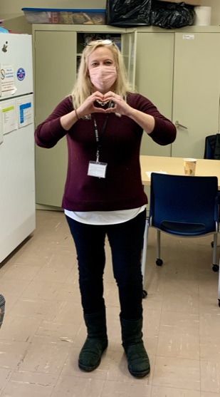 Staff member making a heart with their hands