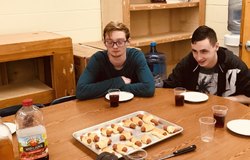 Student at table with cooked hot dogs