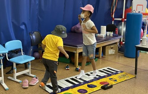 Students playing on the walking piano.