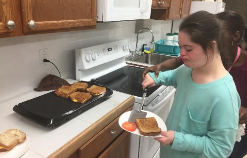 Student putting flap jacks on plate