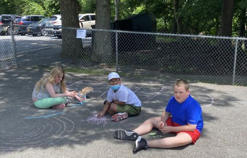 Group of kids drawing with chalk.
