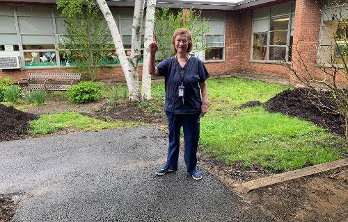 Registered Nurse poses outside.