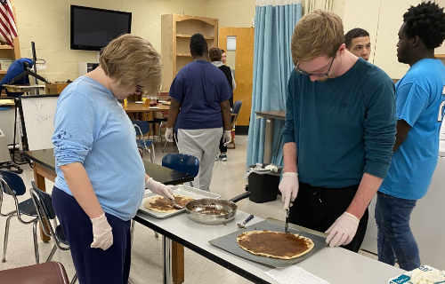 Two students making dessert pizza